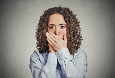 boca cerrada: Primer retrato de joven mujer cubierta cerrada la boca con las manos. No hables mal concepto aislado fondo de la pared gris. Cara emoci�n humana s�mbolo expresi�n. Medios de comunicaci�n empleado relaci�n encubrimiento