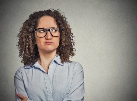 distrust: Displeased suspicious young woman with glasses looking sideways isolated on grey wall background. Negative face expression emotion perception