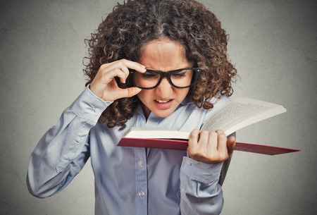 nearsighted: Closeup portrait young woman with eye glasses trying to read book, having difficulties seeing text, bad vision sight problem isolated grey background. Face expression reaction health eyesight issues Stock Photo