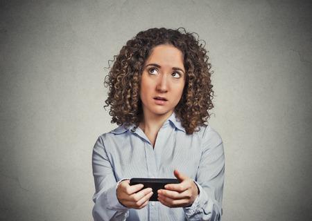 problemas familiares: retrato confundido escépticos mujer de mensajes de texto en el teléfono móvil infeliz disgustado con la conversación para decidir sobre la respuesta aislada fondo de la pared gris. Cara emoción negativa sensación reacción expresión humana Foto de archivo