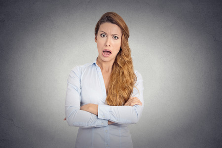 detestable: Pissed of angry young woman with disgusted face expression shouting on grey wall background