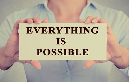 achievable: businesswoman hands holding card with phrase message Everything is possible conceptual of optimism and determination isolated grey office wall background Stock Photo