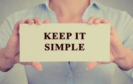 coherent: Retro instagram style image businesswoman hands holding white card sign with keep it simple message text isolated on grey wall office background