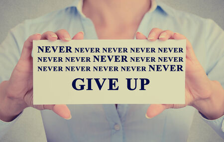 follow through: Retro vintage style image of businesswoman hands holding white card with never give up sign message isolated on grey wall office background.