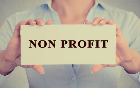 non: Businesswoman hands Holding Small White Sign card with Non Profit Text message
