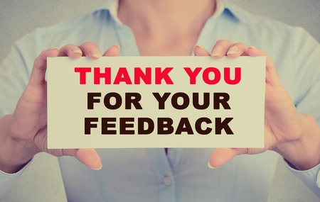 reply: Business woman hands holding white card sign with Thank you for your feedback text message isolated on grey wall office background. Retro style image Stock Photo