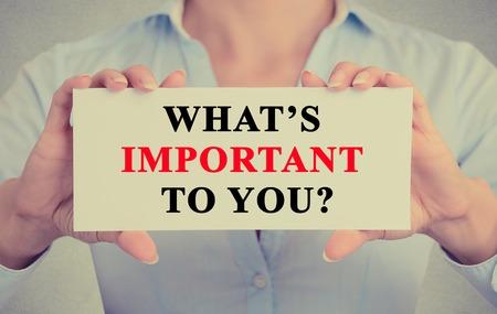 responsabilidad: Empresaria manos la celebración de firmar la tarjeta blanca ¿Qué es importante para usted cuestionan mensaje de texto aislado en fondo gris pared de la oficina. Imagen de estilo retro