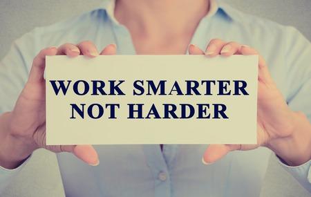 productividad: Trabajar Concepto mejor, no más. Primer estilo retro mujer de negocios imagen Manos celebración de la tarjeta con el texto de motivación frase mensaje escrito en él aislados fondo gris pared de la oficina
