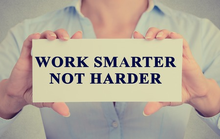 woman work: Work Smarter Not Harder Concept. Closeup retro style image business woman hands holding card with motivational message phrase text written on it isolated grey office wall background Stock Photo
