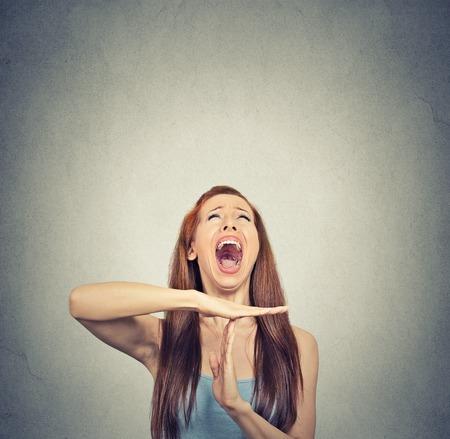 molesto: Mujer joven que muestra el tiempo de espera gesto de la mano, frustrado que grita a stop aisladas sobre fondo gris de la pared. Demasiadas cosas que hacer. Las emociones humanas se enfrentan reacci�n expresi�n