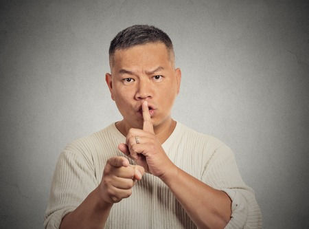 quiet adult: Portrait serious man asking to keep quiet pointing finger at you camera, isolated on grey wall background. Face expression gesture  body language Stock Photo