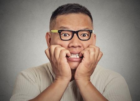 nerveux: Gros plan portrait headshot ringard jeune homme avec des lunettes se rongeant les ongles en vous regardant avec envie de quelque chose ou anxieux isolé sur fond gris mur. La perception d'expression du visage humain