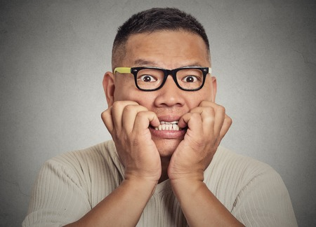 sudoracion: Headshot Retrato del primer chico joven nerd con gafas mordiéndose las uñas que le miran con ansias de algo o ansioso aislado en el fondo de la pared gris. Percepción expresión facial humana