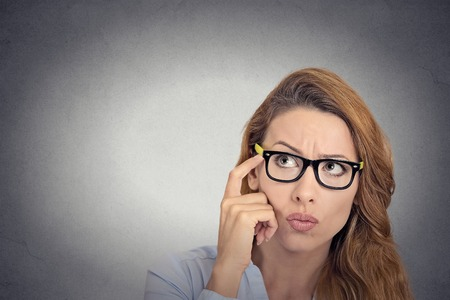 Cant remember. Headshot thoughtful young woman with glasses looking confused isolated grey wall background. Human face expression emotion feelings body language photo