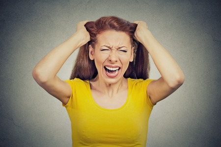 woman shouting: Closeup portrait headshot stressed young housewife, woman, employee, worker having bad day too many things to do tension headache isolated grey wall background. Human face expression emotion reaction