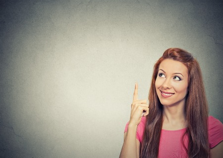 finger: Portrait happy beautiful woman thinking looking up pointing with finger at blank copy space isolated grey wall background. Positive human face expressions, emotions, feelings body language, perception Stock Photo