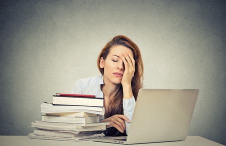 あまりにも多くの仕事疲れ眠い若い女性のラップトップ コンピューターの前に本を持つ彼女の机に座って分離、灰色の壁事務所背景。大学、職場、