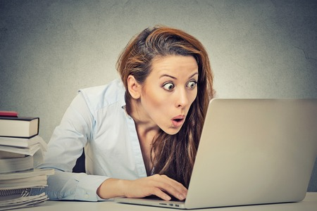 annoyed: Portrait young shocked business woman sitting in front of laptop computer looking at screen isolated grey wall background. Funny face expression emotion feelings problem perception reaction