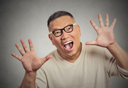 asian man face: closeup super excited funky guy with glasses looking at you arms hands raised at camera isolated grey wall background Stock Photo