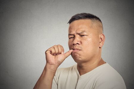 Lazy young man sucking thumb doing nothing isolated on grey wall background. Face expression human emotion photo