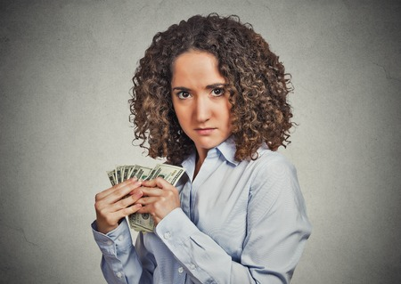 scrooge: Closeup portrait greedy young woman corporate business employee, worker, student holding dollar banknotes tightly isolated grey wall background. Negative human emotion facial expression feeling Stock Photo