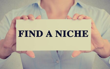 niche: Closeup businesswoman hands holding white card sign with Find a Niche text message isolated on grey wall office background.