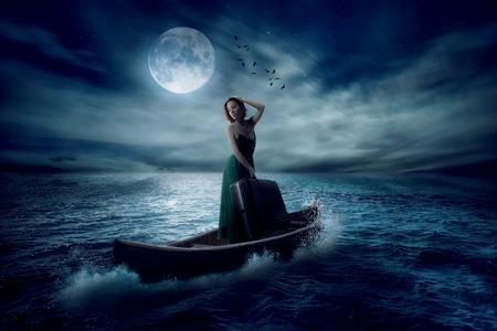 luz de luna: Mujer elegante con maleta que se coloca en el barco en medio oc�ano despu�s de la tormenta a la deriva lejos de luz de la luna las nubes del cielo de fondo. Protector de pantalla paisaje conceptual.