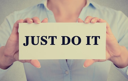 do it: Closeup businesswoman hands holding white card sign with just do it text message isolated on grey wall office background.