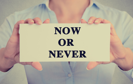 take a note: Businesswoman hands holding white card sign with now or never text message isolated on grey wall office background.