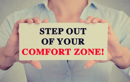 zones: Businesswoman hands holding white card sign with step out of your comfort zone text message isolated on grey wall office background. Retro instagram style image