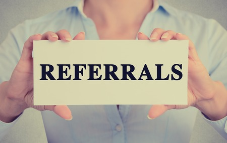 referral marketing: Businesswoman hands holding white card sign with referrals text message isolated on grey wall office background.