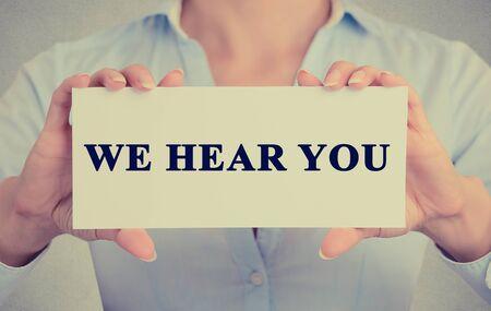 poner atencion: Empresaria manos la celebración de firmar la tarjeta blanca que te escuchen el mensaje de texto aislado en fondo gris pared de la oficina. Foto de archivo
