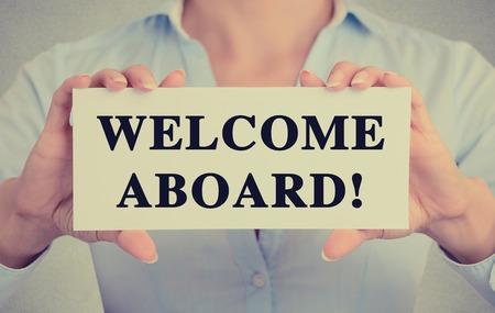 the welcome: Empresaria manos la celebraci�n de firmar la tarjeta blanca con la bienvenida a bordo de mensaje de texto aislado en fondo gris pared de la oficina.