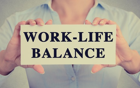 work life balance: Businesswoman hands holding white card sign with work life balance text message isolated on grey wall office background. Retro instagram style image Stock Photo