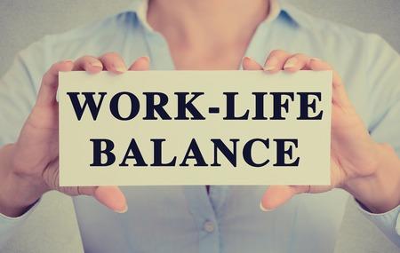balanza: Empresaria manos la celebraci�n de firmar la tarjeta blanca con el mensaje de texto equilibrio trabajo-vida aislada en fondo gris pared de la oficina. Imagen retro estilo Instagram