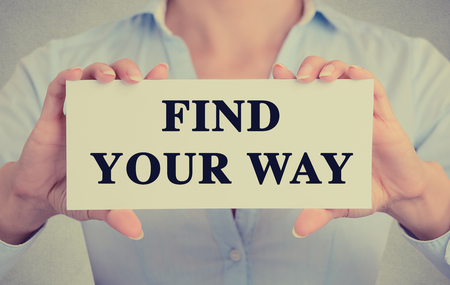 find your way: Closeup businesswoman hands holding white card sign with find your way text message isolated grey wall office background.