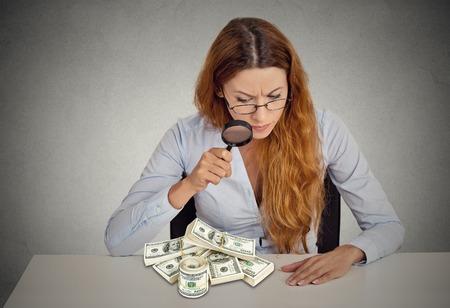 dinero falso: tacaño. Mujer de negocios que mira a través de la lupa en los billetes de pila dólares en la tabla aislado fondo gris oficina. Economía concepto de éxito riqueza financiera. Ponzi investigación esquema