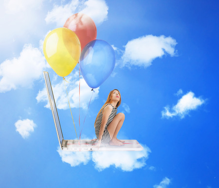 Young woman sitting on laptop computer with fun colorful balloons flying high in blue sky photo