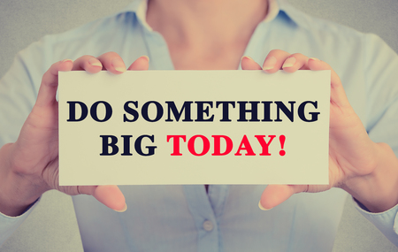 possibility: Businesswoman hands holding white card sign with do something big today text message isolated on grey wall office background.