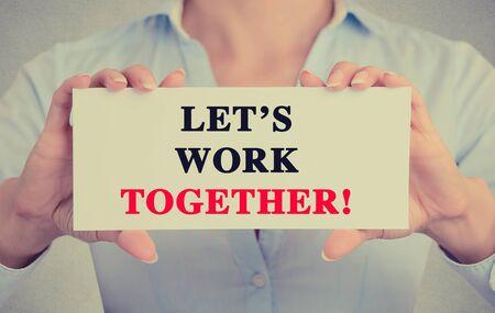 mision: Empresaria manos la celebraci�n de firmar tarjeta blanca con Trabajemos juntos mensaje de texto aislado en fondo gris pared de la oficina.