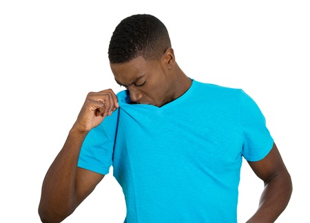 stinks: Closeup portrait young Man, Smelling sniffing Armpit, something Stinks very bad, foul Odor situation isolated grey, black background. Negative human emotions, facial expressions, feeling body language
