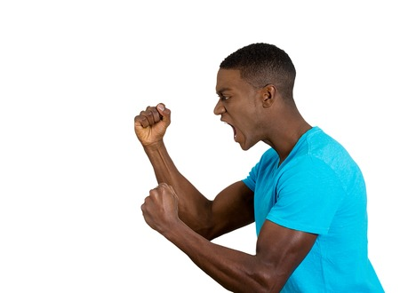 Closeup side view profile portrait angry upset young man worker business employee fists in air open mouth yelling screaming isolated white background. Negative emotion face expression feeling Stock Photo