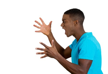 bad temper: Closeup side view profile portrait angry upset young man worker business employee fists in air open mouth yelling screaming isolated white background. Negative emotion face expression feeling Stock Photo