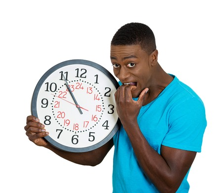 test deadline: Closeup portrait funny looking man student holding wall clock, stressed biting fingernails pressured by lack, running out of time, late meeting, interview, appointment isolated white background. Emotion