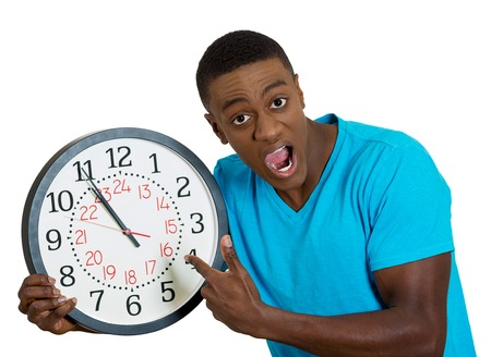 running out of time: Closeup portrait funny looking man student holding wall clock, stressed biting fingernails pressured by lack, running out of time, late meeting, interview, appointment isolated white background. Emotion