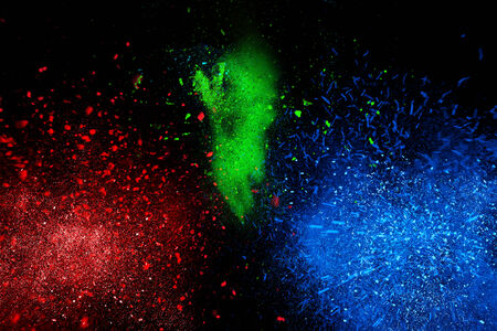 dust cloud: Freeze motion of colorful powder exploding, isolated on black, dark background. Abstract design of dust cloud. Particles explosion, screen saver wallpaper with copy space. Vivid yellow green red ash