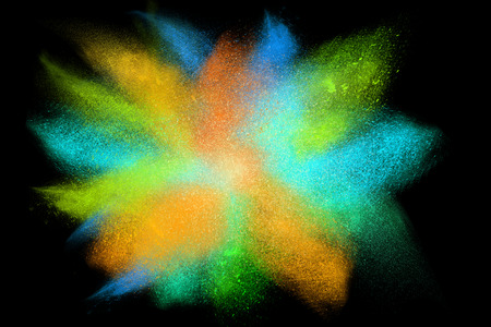 shatter: Freeze motion of colorful powder exploding, isolated on black, dark background. Abstract design of dust cloud. Particles explosion, screen saver wallpaper with copy space. Vivid green orange blue ash