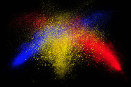 ash cloud: Freeze motion of colorful powder exploding, isolated on black, dark background. Abstract design of dust cloud. Particles explosion screen saver wallpaper with copy space. Vivid red, blue, yellow ash.