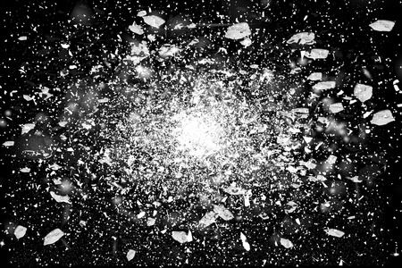 Freeze motion of white powder exploding, isolated on black, dark background. Abstract design of white dust cloud. Particles explosion screen saver, wallpaper with copy space. Planet creation concept