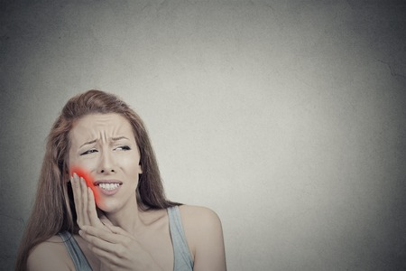 Primer retrato de mujer joven con el diente sensible problema corona dolor a punto de llorar de dolor de tocar área roja fuera de la boca con la mano aislado fondo gris. La emoción negativa sensación expresión de la cara